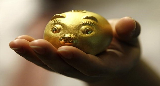 An employee of a jewellery shop holds a 112.5 gram-weight gold pig during a photo opportunity at a jewellery shop at the Shinsegae department store in Seoul